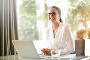 Woman sitting in front of computer smiling